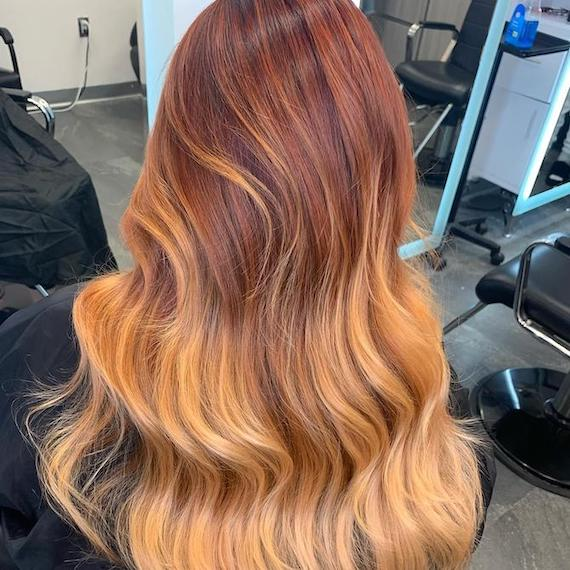 Back of woman's head with long, wavy, ginger peach hair, created using Wella Professionals.