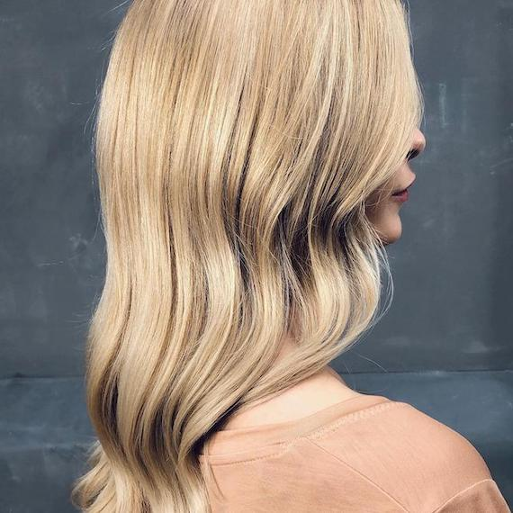 Side profile of woman with long, wavy, buttercream blonde hair, created using Wella Professionals.