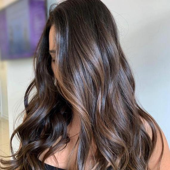 Woman with long, brunette hair and brown balayage, created using Wella Professionals.