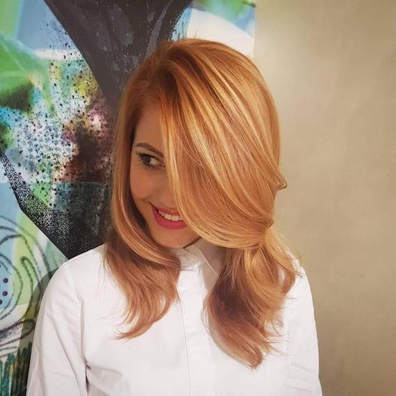 Woman wearing white shirt and showing off strawberry blonde highlights, created using Wella Professionals.