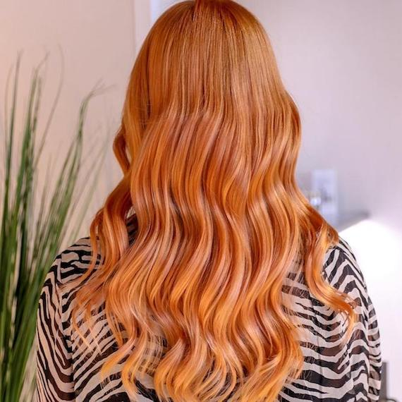 Back of a woman's head showing long, wavy, strawberry blonde ombre hair, created using Wella Professionals.