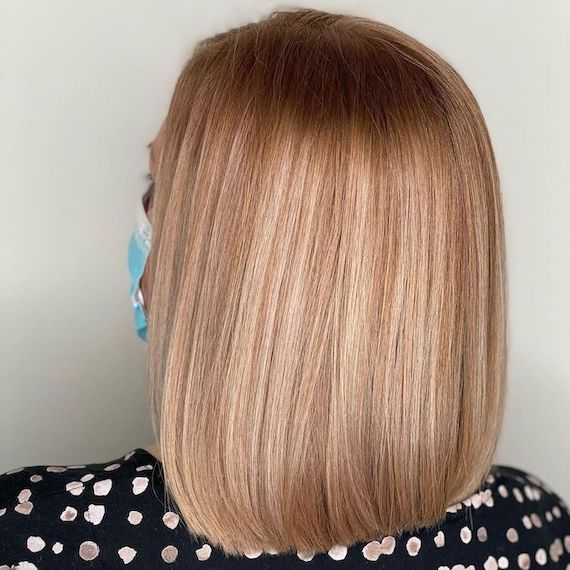Back of woman's head with amber blonde hair and retouched roots, created using Wella Professionals.