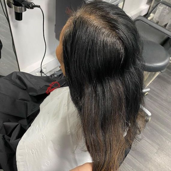 Back of woman's head with long, black hair and grown-out gray roots.