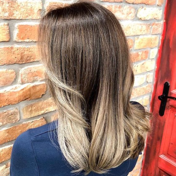 Back of woman's head with ash brown roots and ash blonde balayage, created using Wella Professionals.