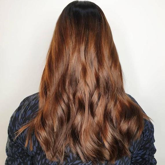 Model with long, brown, wavy hair and subtle highlights, created using Wella Professionals.