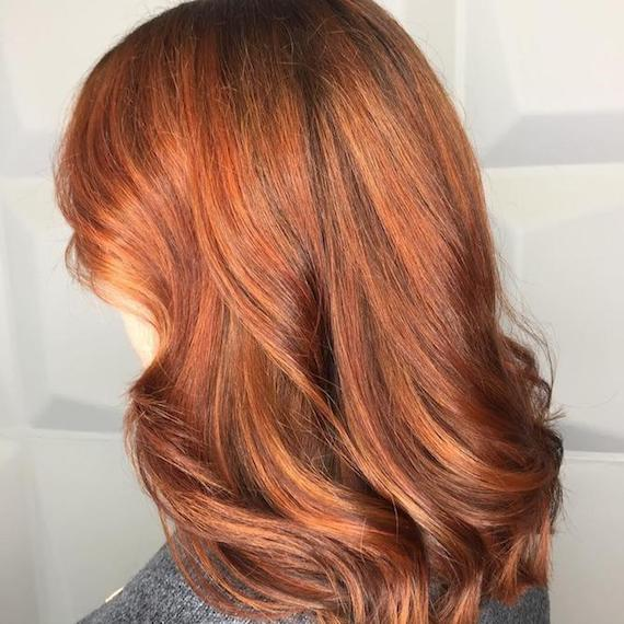 Model with mid-length, red, wavy hair and subtle copper highlights, created using Wella Professionals.