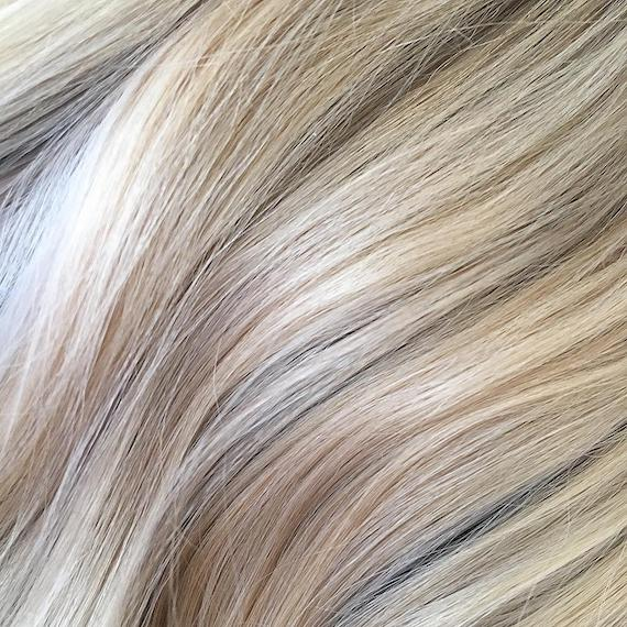 Close-up images of multi-tonal blonde hair color with a soft wavy texture, created using Wella Professionals.