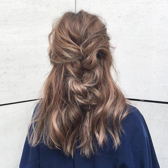 Photo of the back of a woman's head with tousled brunette hair and blonde highlights, tied into a loose plait. Look created by Wella Professionals.