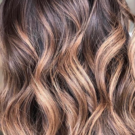 Close-up image of balayage hair color, styled in loose curls, created by Wella Professionals.
