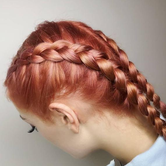 Close-up image of side of woman's head, wearing pink hair color and boxer braids, created by Wella Professionals.