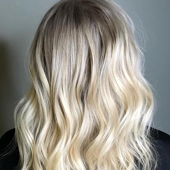 Image of the back of a woman's head, showing light blonde hair color and loose, natural-looking waves, created by Wella Professionals.