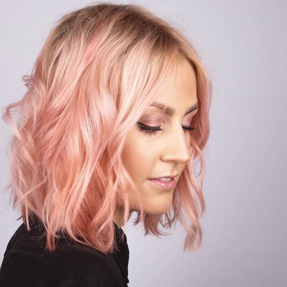 Side profile of a woman with a peach, wavy bob, styled using Wella Professionals