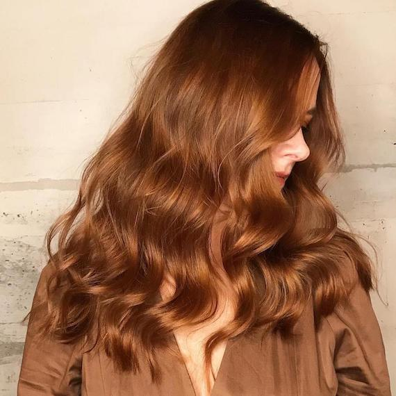 Side profile of a woman with loose wavy hair, styled using Wella Professionals