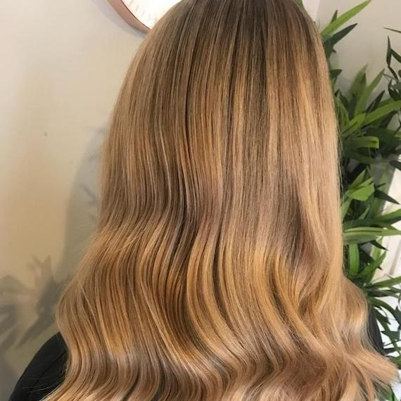 Back of a woman's head showing dark blonde hair, created using Wella Professionals