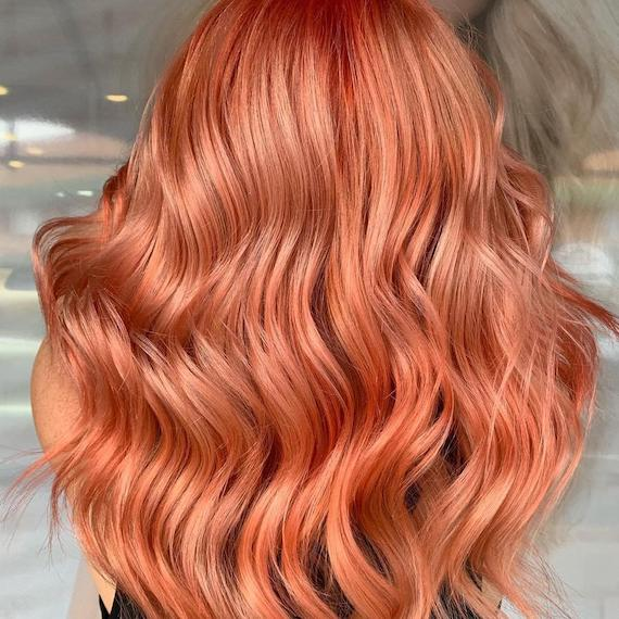 Back of a woman's head showing wavy, peach hair, created using Wella Professionals