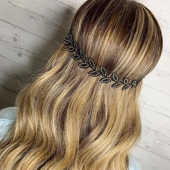 Back of a woman's head showing a boho headband placed over wavy hairstyle, styled using Wella Professionals