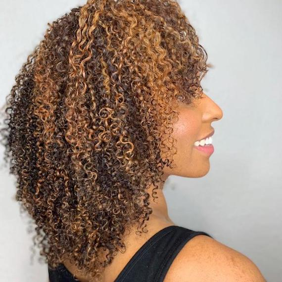 Side profile of a woman with defined curly hair, styled using Wella Professionals