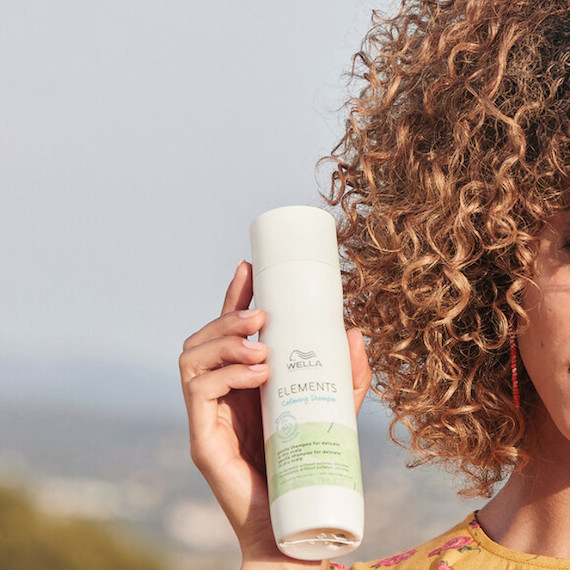 Model with curly hair holding up Wella Professionals Elements Shampoo.