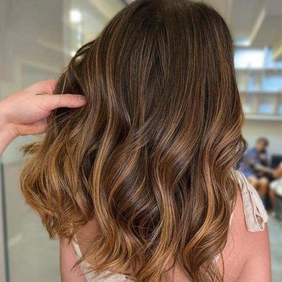 Back of woman's head with long, wavy chocolate brown hair and golden twilights, created using Wella Professionals.