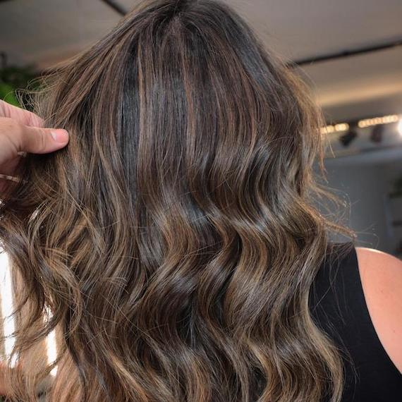 Back of woman's head with long, wavy brunette hair and subtle twilights, created using Wella Professionals.