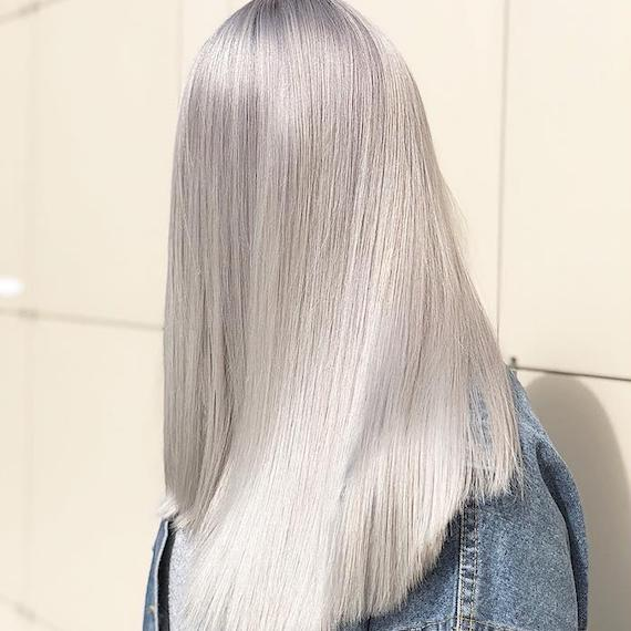 Photo showing the back of woman's head with super-straight, long, icy blonde hair. Created using Wella Professionals.