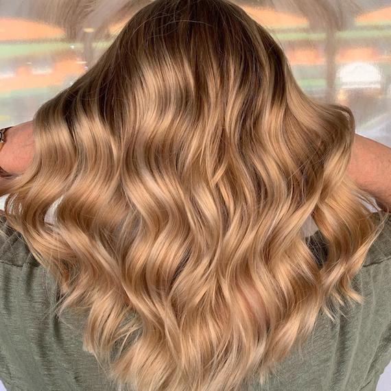 Photo showing the back of a woman's head with long, wavy, balayage hair. Created using Wella Professionals.