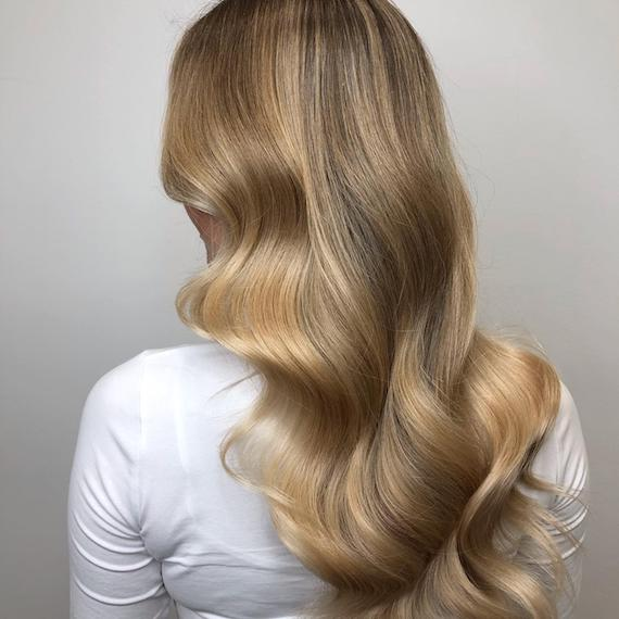 Photo showing the back of a woman's head with long, loosely-curled, dark blonde hair. Created using Wella Professionals.