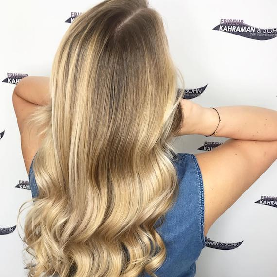 Photo showing the back of model's head with long wavy warm blonde hair. Created using Wella Professionals.
