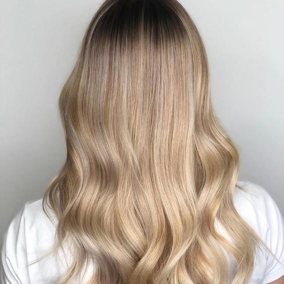 Photo showing the back of a woman's head with long, loosely-curled, creamy blonde hair. Created using Wella Professionals.
