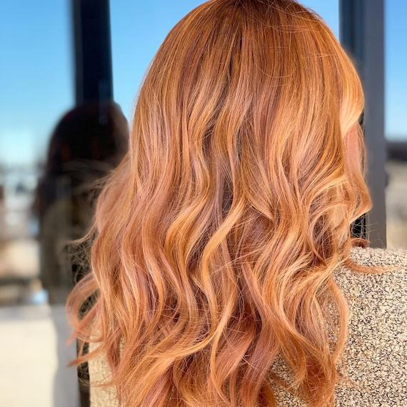 Photo showing the back of a woman's head with long, wavy, strawberry blonde hair. Created using Wella Professionals.