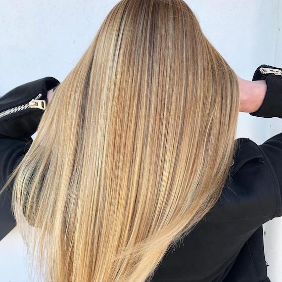 Photo showing the back of a woman's head with long, super-straight, golden blonde hair. Created using Wella Professionals.