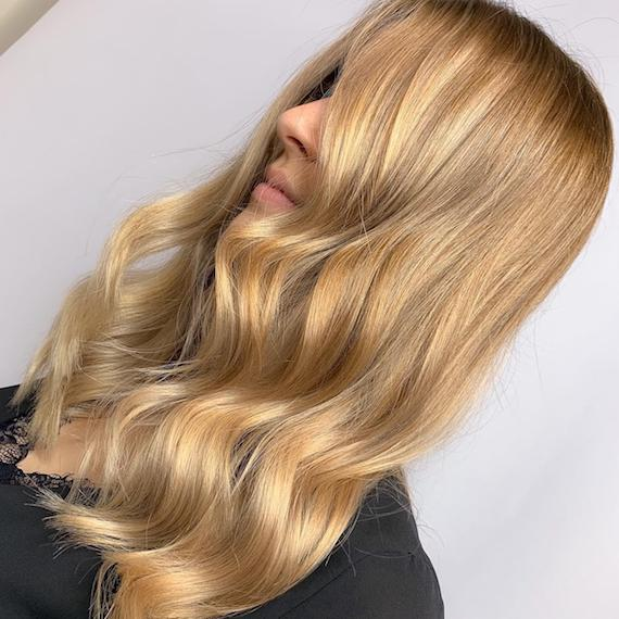 Side profile of a woman with long, wavy, honey blonde hair. Created using Wella Professionals.