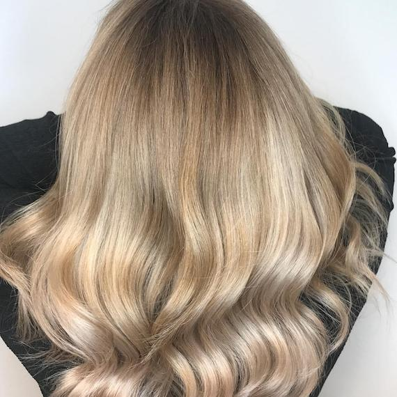 Photo showing the back of a woman's head with long, loosely-curled, beige blonde hair. Created using Wella Professionals.