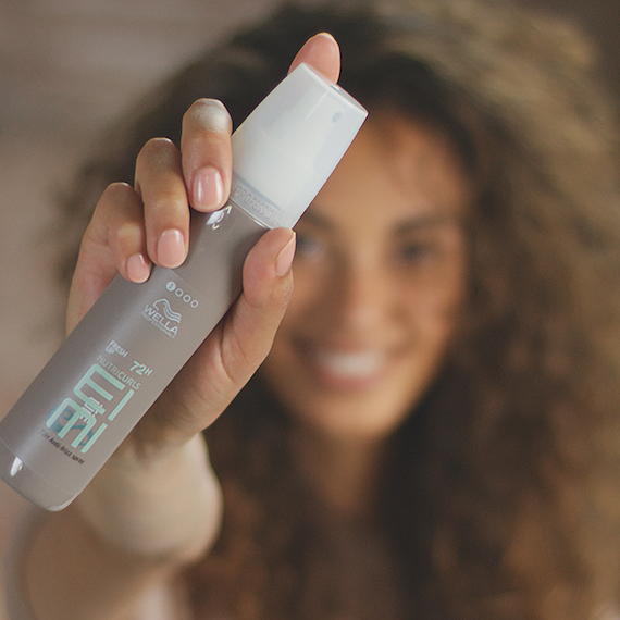 Model holding Wella Professionals EIMI Fresh Up 72h Anti-Frizz Spray