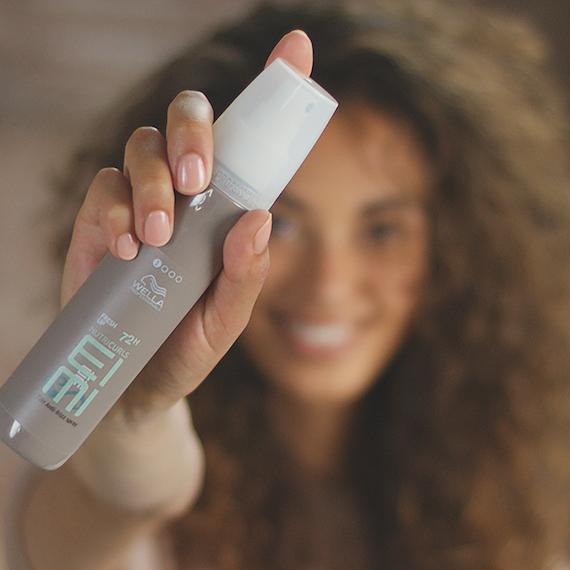 Model holding Wella Professionals EIMI Fresh Up 72h Anti-Frizz Spray
