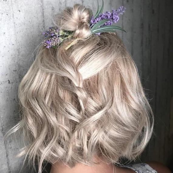 Photo of the back of a woman's head with hair styled half-up wedding hairstyle that's decorated with flowers, created using Wella Professionals