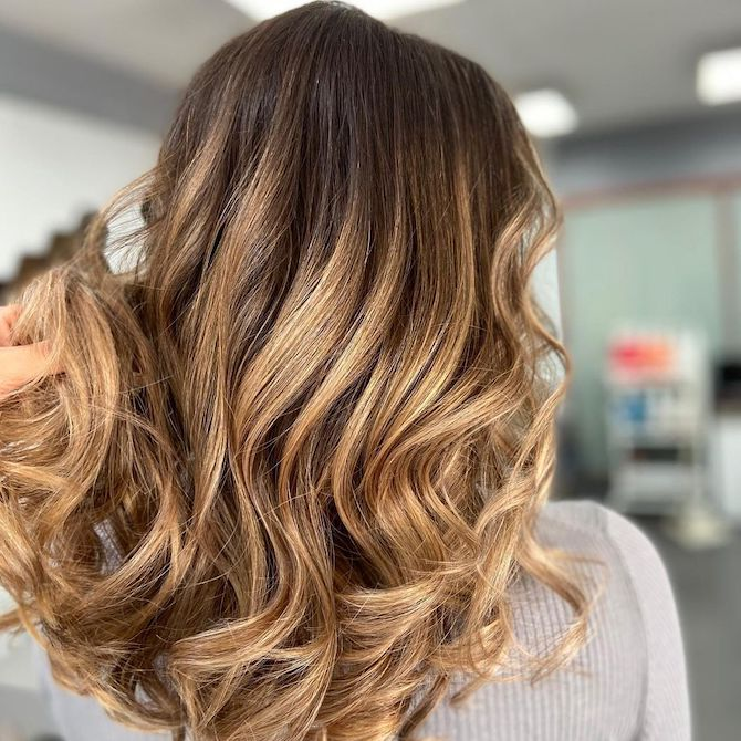 Back of woman's head with loosely curled hair and caramel balayage.