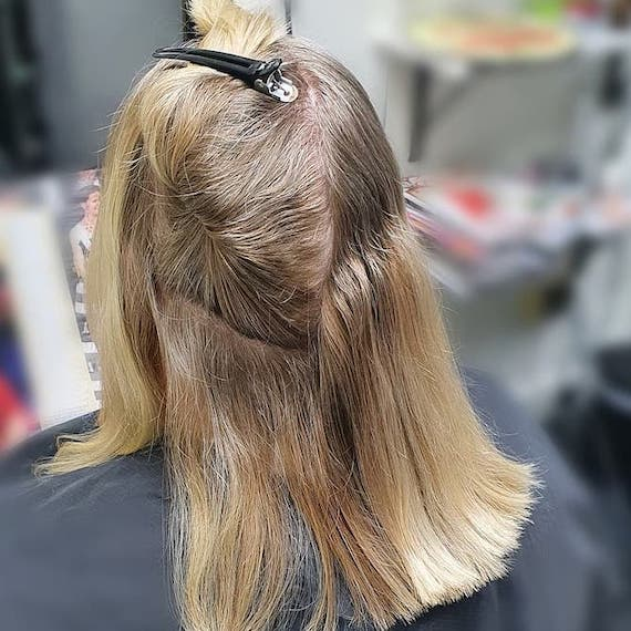 Back of woman's head with shoulder-length blonde hair and grey roots, sitting in a salon chair.