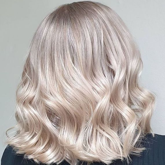 Back of woman's head with loosely curled, ice blonde hair.