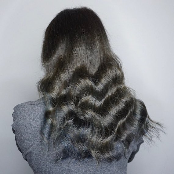 Photo of the back of a woman's head with blue black hair color. Look created by Wella Professionals.