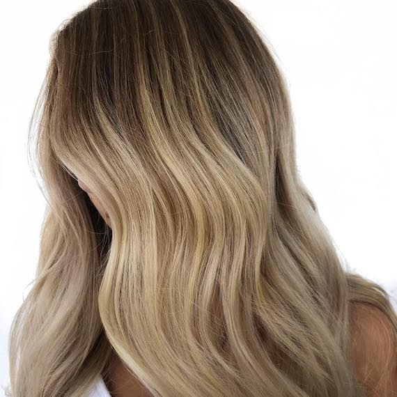 Image of woman's hair with dark blonde ombre hair color. Look created by Wella Professionals.
