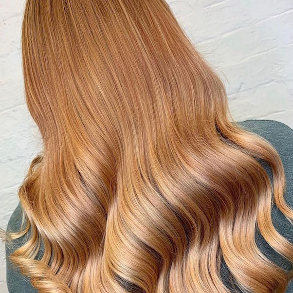 Back of woman's head with long, wavy, strawberry blonde hair, created using Wella Profes-sionals.