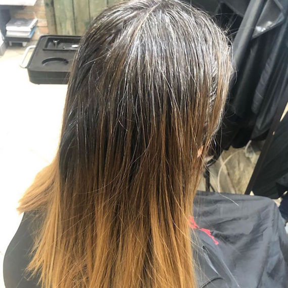 Back of woman's head with long, gray roots and warm blonde mid-lengths.