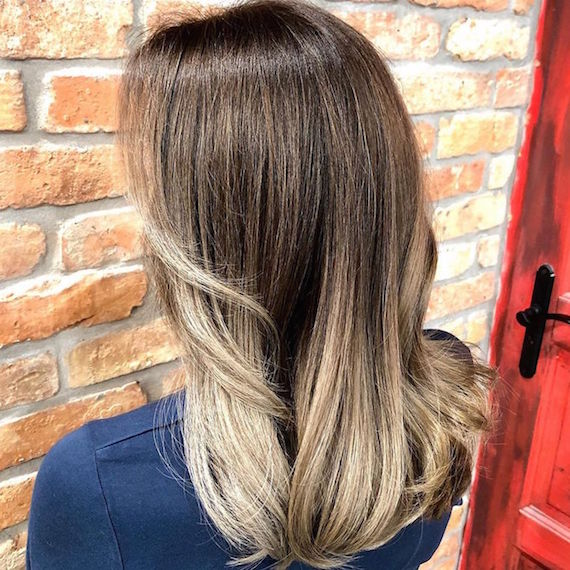 Back of woman's head with long, ash blonde balayage, created using Wella Professionals.