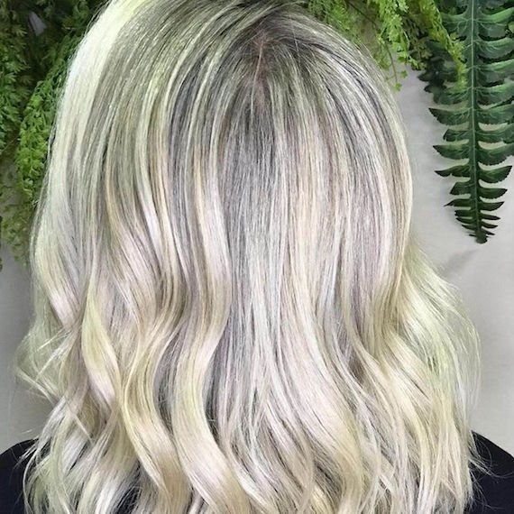 Back of woman's head with wavy platinum blonde hair, created using Wella Professionals.
