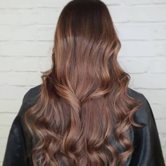 Back of woman's head with long, loosely-curled, brunette hair, created using Wella Profes-sionals.