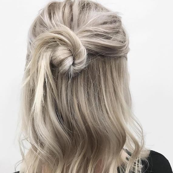 Back of a woman's head with hair styled in an ash blonde, half-up bun, created using Wella Professionals