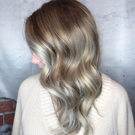 Side profile shot of woman with loosely-curled, ash blonde hair, created using Wella Professionals