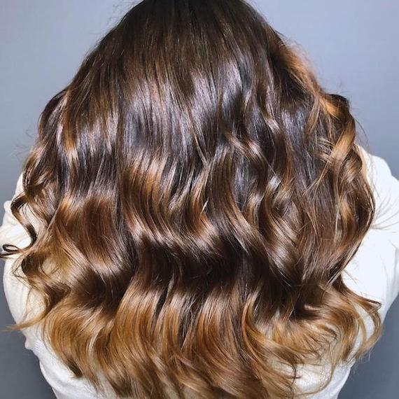 Close-up of the back of a woman's head with long and wavy chocolate brown hair