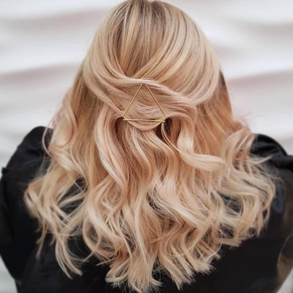Back of woman's head with long, wavy hair decorated using bobby pins, created with Wella Professionals.